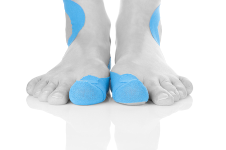 Kinesio tape on female foot isolated on white background.
