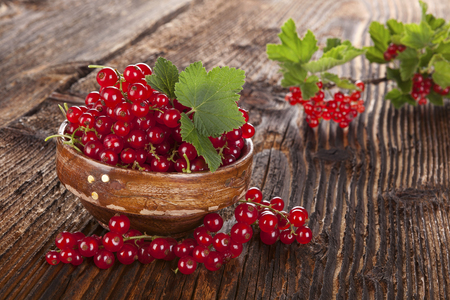 red currant: Red currant on wooden background.