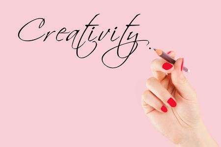 caligraphy: Female hand with pencil writing the word creativity in caligraphy.