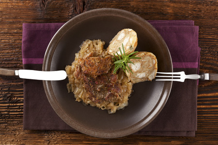silver cutlery: Baked pork chop with dumplings and sauerkraut on plate with silver cutlery on wooden table, top view.