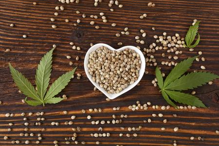 Hemp seeds on wooden background, top view.