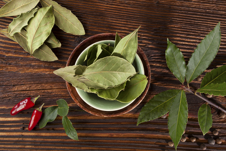 condiment: Bay leaves, traditional spice and condiment wooden background.