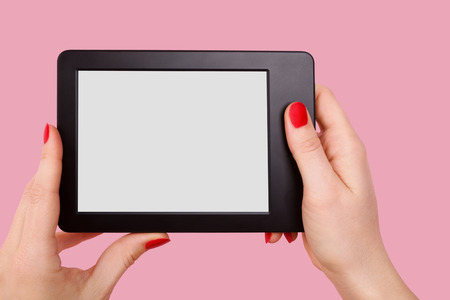 e reader: Female hand holding e reader isolated on pink background.