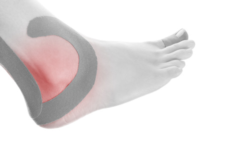 therapeutic: Therapeutic tape on female ankle isolated on white background. Chronic pain, alternative medicine. Rehabilitation and physiotherapy. Stock Photo