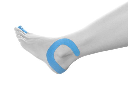therapeutic: Therapeutic tape on female ankle isolated on white background.