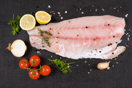 Luxurious perch fillet on black background, top view. Culinary fish eating. Archivio Fotografico