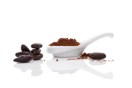 cocoa beans: Cocoa beans and cocoa powder in white bowl and white spoon on white background. Healthy superfood. Stock Photo