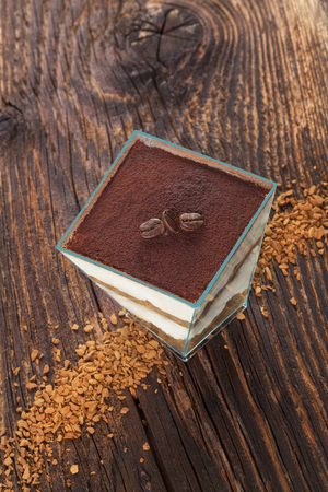instant coffee: Tiramisu dessert with coffee beans and instant coffee on wooden textured table. Traditional tiramisu dessert, rustic, country style. Stock Photo