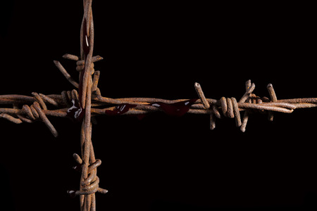 barb wire isolated: Rusty barb wire cross isolated on black background. Religious wars. Stock Photo
