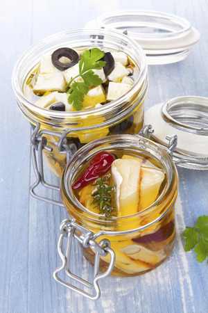 Marinated cheese in glass jar on blue wooden background. Culinary cheese eating. Stok Fotoğraf