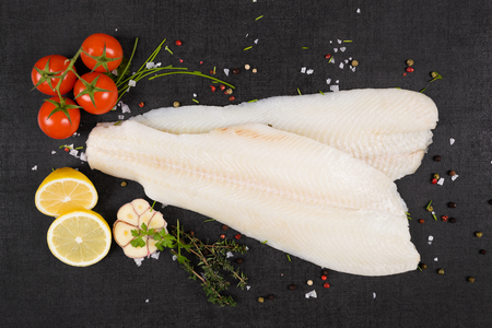 Fresh halibut fillet with fresh herbs and garlic on dark black stone background top view. Luxurious seafood eating background. Фото со стока