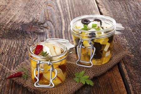 カマンベールと木製のテーブルにガラスの瓶に油でギリシャの偉業チーズのマリネ。伝統的な料理のチーズを食べる。