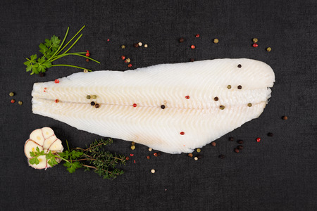 luxurious: Fresh halibut fillet with fresh herbs and garlic on dark black stone background top view. Luxurious seafood eating background. Stock Photo