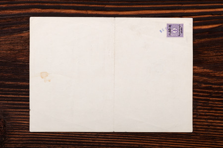 old envelope: Old envelope with stamp on brown wooden table, top view. Stock Photo