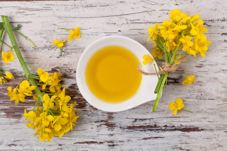 Rapeseed oil and flowers on wooden background, top view.