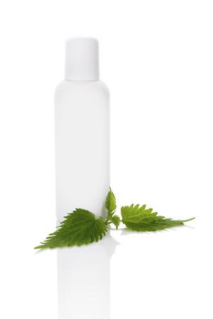 stinging  nettle: Stinging nettle cosmetics mockup. Fresh stinging nettle leaves and white plastic bottle without label isolated on white background.