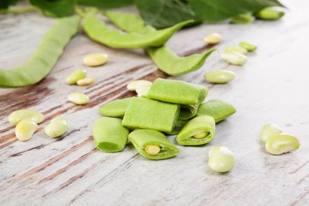 Sliced green beans on white wooden table. Healthy legume eating. Reklamní fotografie