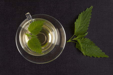 Fresh stinging nettle tea and leaves on black background, top view. Alternative herbal remedy.