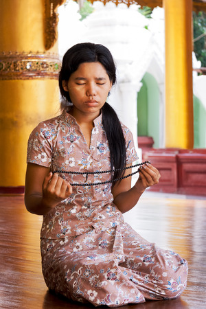 Young beautiful girl meditates in buddhist temple in Myanmar, Asia. Yangon, Myanmar. Wanderlust. Discovering the world. Editorial