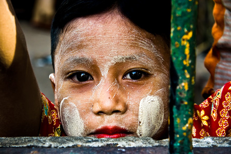Colors of Myanmar. Portrait of young girl wearing traditional thanaka cream on face.
