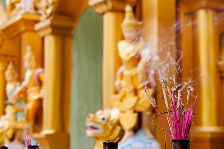 Incense sticks burning in buddhist temple in Yangon, Myanmar, Asia.