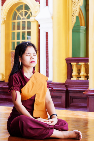 Young buddhist nun meditates in temple in  Rangoon, Myanmar, Asia. Wanderlust. Discovering the world. Editorial