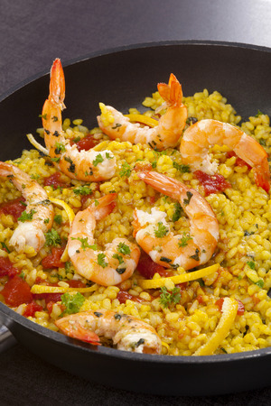 marisco: Delicious paella food in black pan with shrimps.Typical spanish dish.