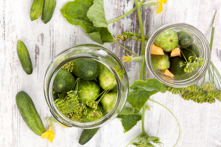 cucumis sativus: Pickles. Fresh cucumbers in glass on white wooden table from above. Vintage, rustic style. Stock Photo