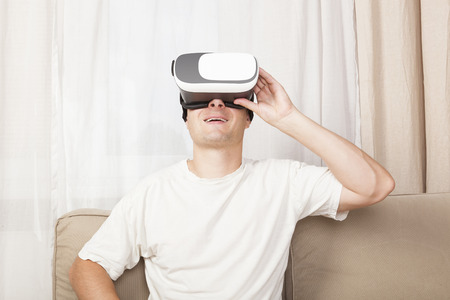 Young handsome man in Virtual Reality on sofa. Virtual reality porn. Stock Photo