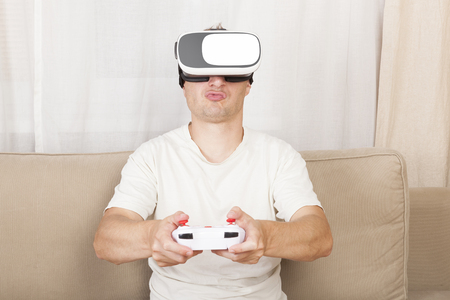 simulations: Handsome man with VR headset playing virtual reality in living room. Future of technology.