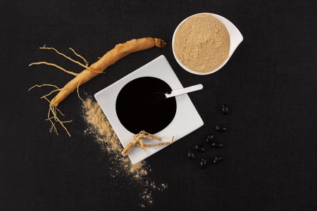 Ginseng root, extract, powder and pills on black background top view. Adaptogen, natural remedy. Stock Photo