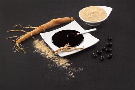 Gezonde Ginseng-supplementen. Verse wortel, pillen, uittreksel en poeder op zwarte achtergrond. Stockfoto