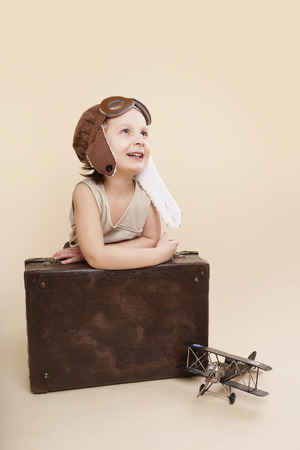 Cute girl with retro leather pilot hat, vintage airplane and antique suitcase isolated.