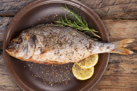 gilt head: Grilled fish on brown plate on textured wooden background, top view. Mediterranean luxurious seafood concept. Stock Photo