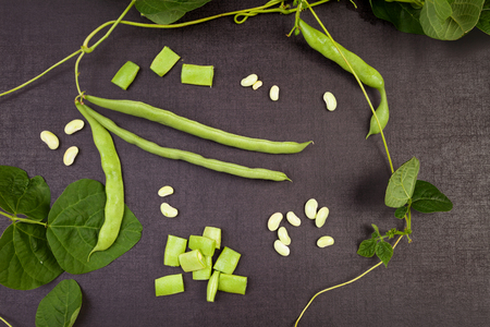 Raw green string beans, whole and sliced, black surface. Healthy legumes eating.