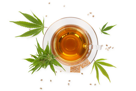 Cannabis tea with crackers from above with cannabis plant and leaves, isolated on white background. Alternative medicine, medical cannabis, natural remedy. Stock Photo