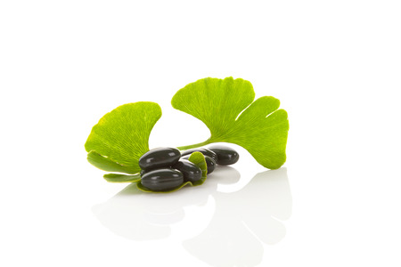 Ginkgo leaves with gel capsules on white background with reflection. Alternative medicine, nutritional supplement.