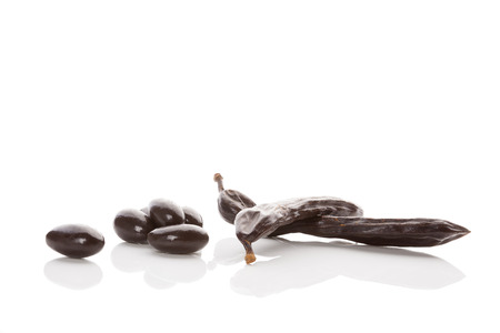 Carob pod and sweets isolated on white background. Healthy sweets eating.