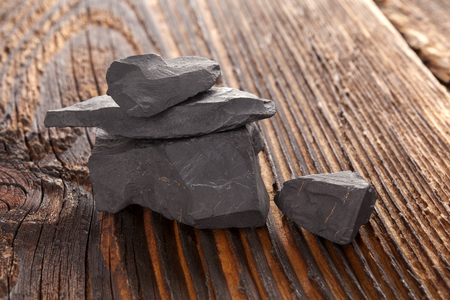 Shungit stone on dark wooden background. Natural water cleaner.