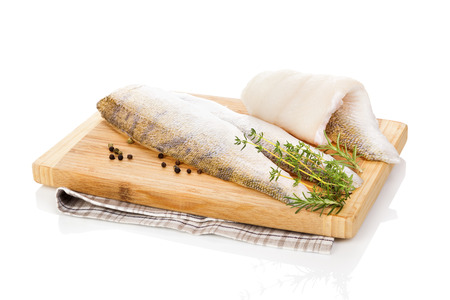 Fillet fish slices on wooden chopping board isolated on white background. Luxurious seafood eating.