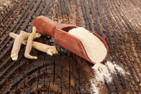 Sshwagandhapoeder en wortel op houten lijst. Superfood, alternatieve geneeskunde, natuurlijke remedie. Stockfoto