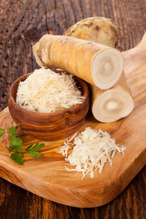 Fresh and grated horseradish in wooden bowl with parsley on wooden background..