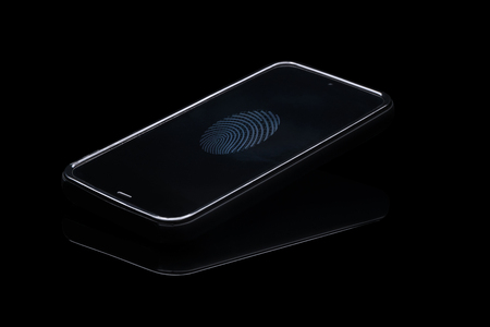 Fingerprint identification on cellphone. Smartphone isolated on blak background with fingerprint icon on screen. Stock Photo