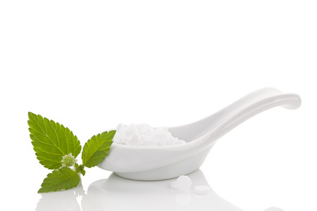 Artificial sweetener pills in white spoon and aztec sweet herb isolated on white background. Sugar substitute. Natural and artificial sweetener. Stok Fotoğraf