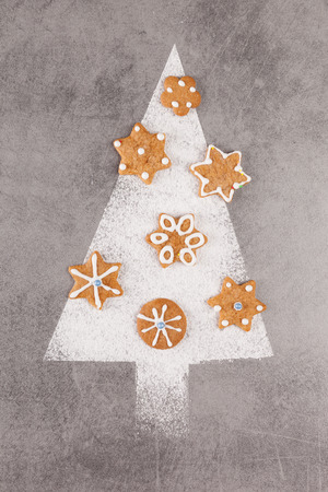 Christmas tree made from powdered sugar with gingerbread cookies. Flat lay, from above.