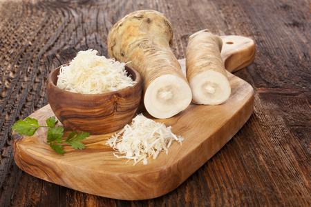 Verse en geraspte mierikswortel in houten kom met peterselie op houten snijplank. Paardenradijswortel. Stockfoto