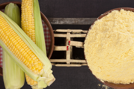 Corn cobs and corn flour on old weight scale from above. Dark surface.