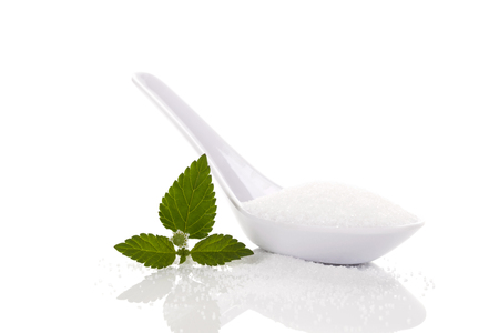 White Crystallized Sugar in white spoon isolated on white background with aztec sweet herb leaf.