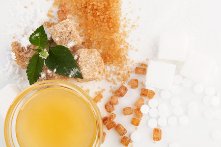 Various types of sugar -  brown, white, crystal, powdered and cane sugar, artificial sweetener and honey in bowl.