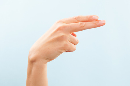 American sign language. Female hand showing letter H isolated on blue background.  Foto de archivo